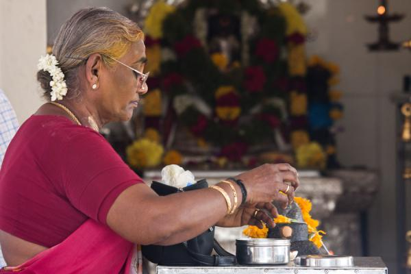 Woman performing religious rituals at Sri Mariamman temple | Templo de Sri Mariamman | Singapur