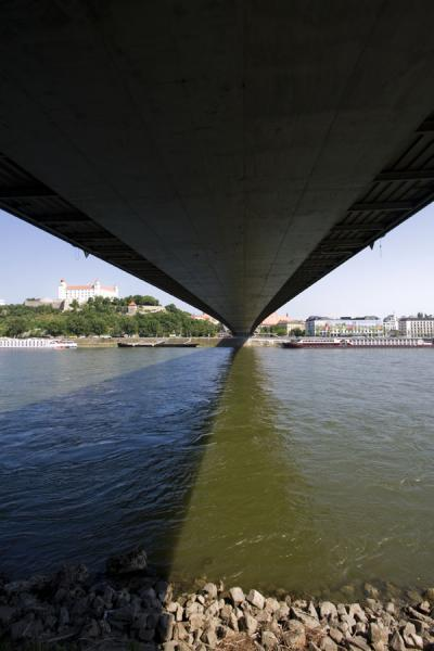 Looking at the New Bridge from below, with the Danube, and Bratislava Castle in the background | Bratislava New Bridge | Slovakia