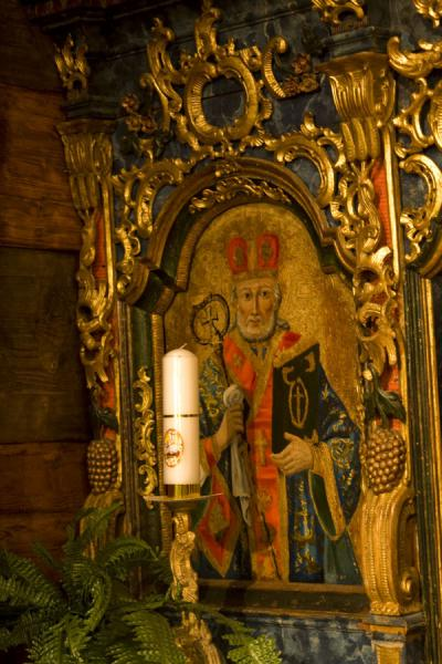 Icon with saint and candle in a corner of the wooden church of Jedlinka | Protection of Mother of God church | Slovakia