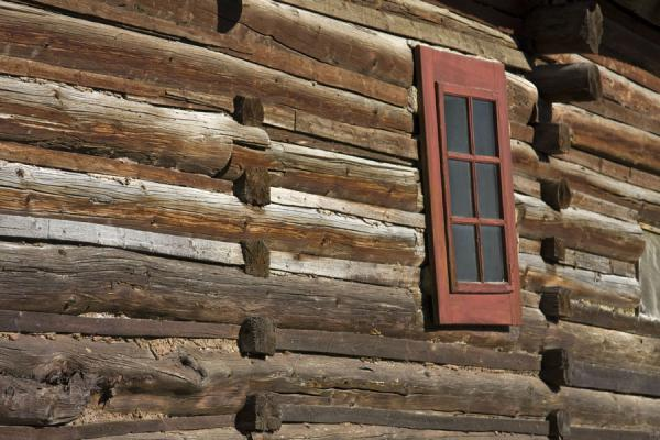 Red window in the wall of a rustic wooden cabin | Vlkolínec | Slovakia
