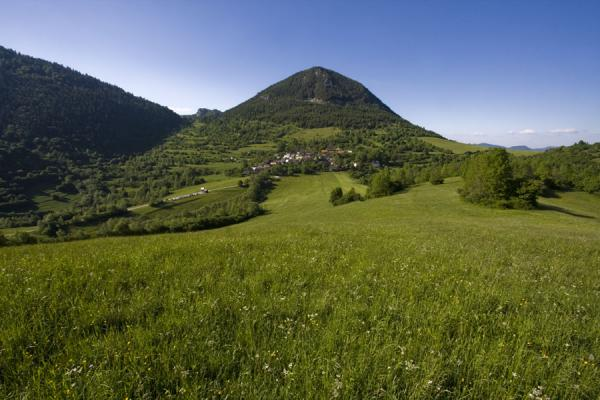 Picture of Vlkolínec in the middle of a green landscape with grass, trees, and mountains