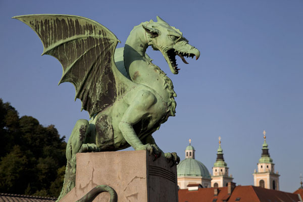 The Ljubljana dragon, symbol of the city, on the Dragon Bridge with the Cathedral of St Nicholas in the background | Ljubljana Old Town | Slovenia