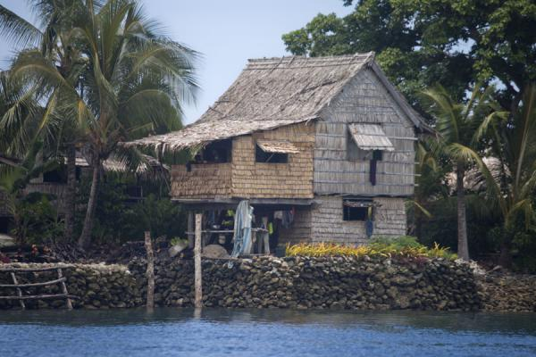 Foto van One of the many houses protected against the sea by a coral wallTalakali - Salomonseilanden