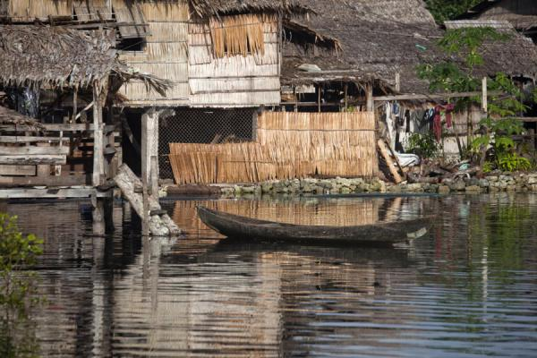 Dugout canoe moored to one of the huts on the brook of Lilisiana | Lilisiana | Solomon Islands
