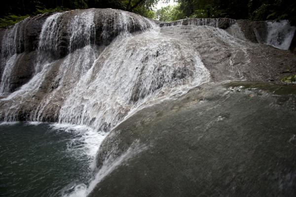 One of the pretty parts of Mataniko falls, with water rushing over boulders into a pool | Mataniko Falls | Solomon Islands