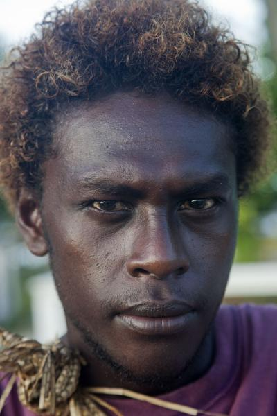 Serious look of a guy in the early morning at the airfield of Gizo | Solomon Island people | Solomon Islands