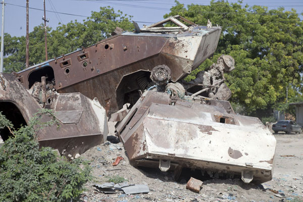 Picture of Armoured personnel carriers rusting away on a corner of a street in the dusty streets of Mogadishu