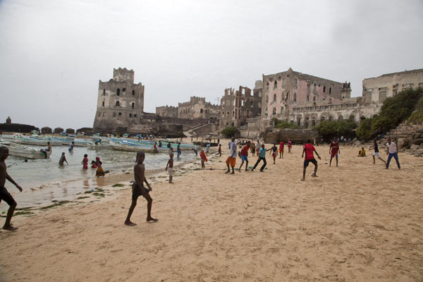Foto van Kids playing football on the beach with the lighthouse at the far sideMogadishu - Somalië