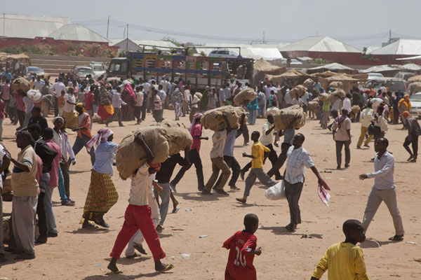 Foto van People rushing from the trucks with a fresh supply of qat to the marketMogadishu - Somalië