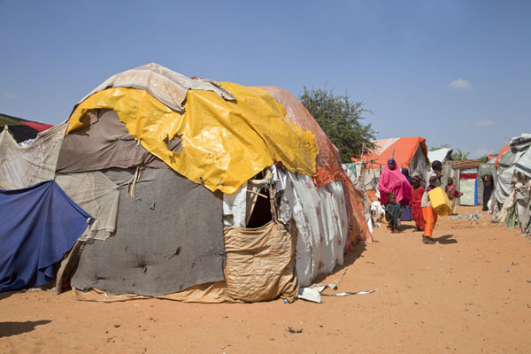 Refugees walking past a row of make-shift tents in their camp | Camp de réfugiés Mogadiscio | Somalie