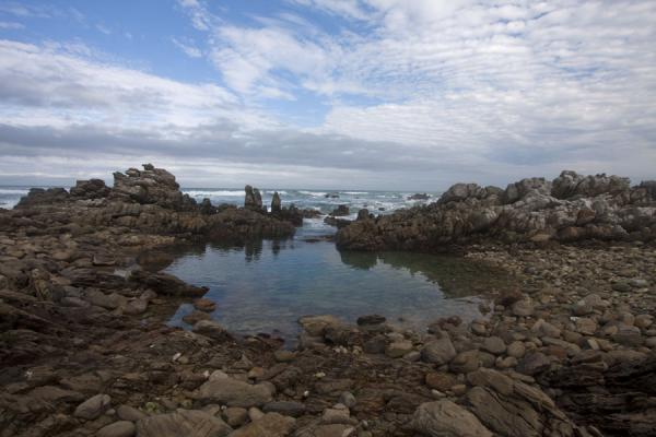 Coastline near to the southernmost tip of Africa with small pool with rocks | Cape Agulhas | South Africa