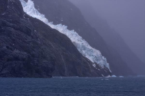 Glacier tumbling down the steep rocks on the side of Drygalski Fjord | Drygalski Fjord | South Georgia and South Sandwich Islands