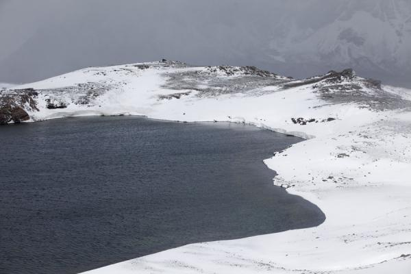 Picture of Lake with snowy banks above Fortuna Bay