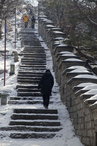 People walking up the snowy stairs towards Seojangdae command post | Hwaseong fortress | South Korea