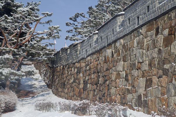 The wall of Hwaseong fortress in a snowy forest at Seonamilchi bastion | Hwaseong fortress | South Korea