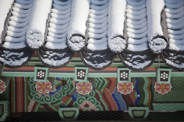Close-up of colourfully painted roof with snow at Seojangdae command post | Hwaseong fortress | South Korea