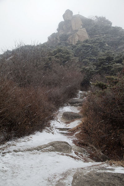 Looking up a snowy trail and granite rocks on Inwangsan | Inwangsan | South Korea