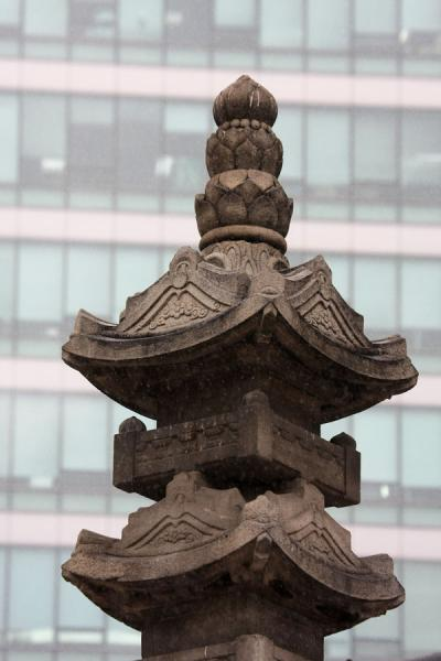 Picture of Jogyesa Temple (South Korea): Top of seven story stone stupa with modern building in the background