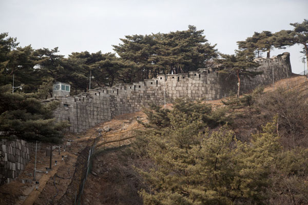 The city wall with fence leading up towards Gokjang | Mount Bugaksan City Wall | South Korea