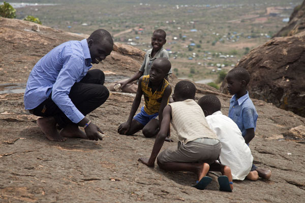 Foto van Zuid Soedan (Kids looking as student writes his name on the surface of the rocks on Jebel Kujul)