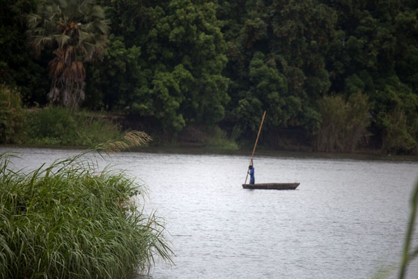 Young man with pole on a wooden canoe on the river Nile | Juba Snapshots | South Sudan