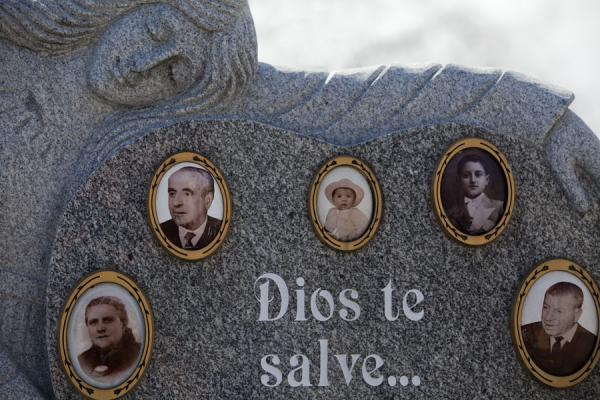 Foto de Close-up of tombstone with woman and pictures of the deceased at one of the many graves of Almudena cemeteryMadrid - España