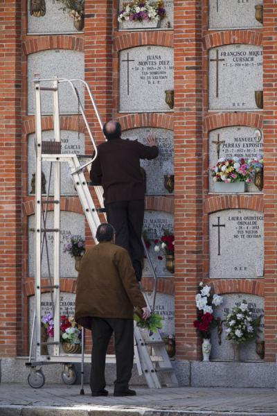 Men using stairs to add flowers to one of the graves in a wall | Almudena Cemetery | Spain
