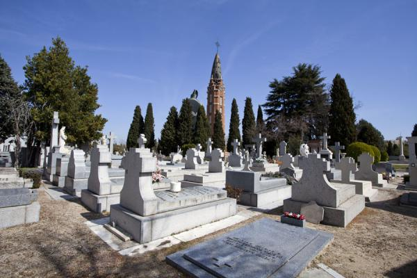 Graves in the foreground and the tower of the chapel in the background | Almudena Cemetery | Spain