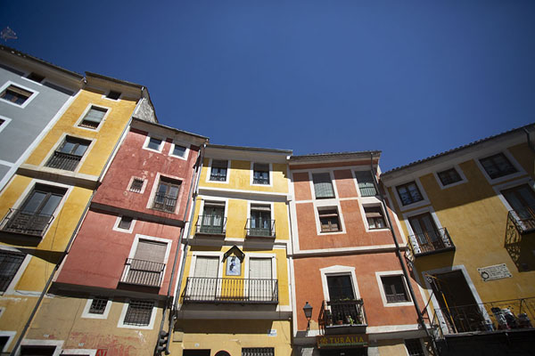 Looking up the colourful houses in the Calle Alfonso VIII | Cuenca old town | Spain