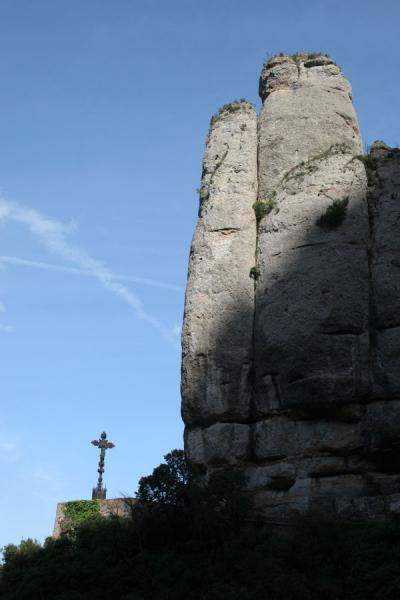Steep cliffs rising above an iron cross in the mountains of Montserrat | Montserrat | Spain
