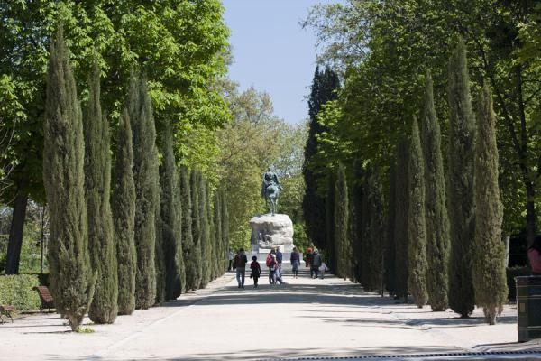 One of the stately lanes surrounded by trees, with Monument to General Arsenio Martínez Campos in the background | Parque del Buen Retiro | Spanje