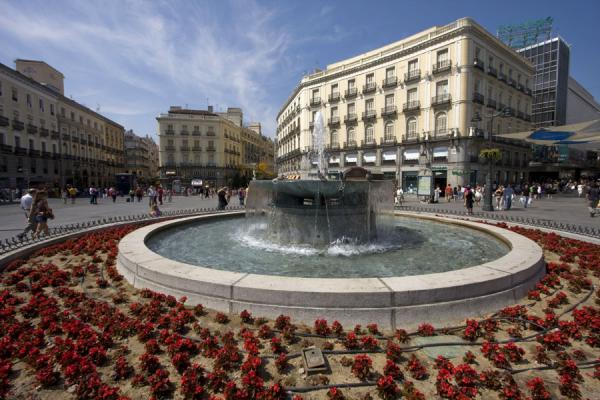 Picture of Puerta del Sol (Spain): Flowerbed and fountain with part of the Puerta del Sol