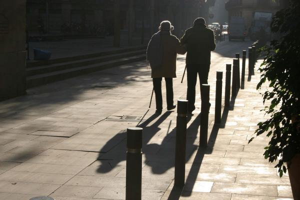 Picture of Old couple walking the streets of Sant Pere with their shadows