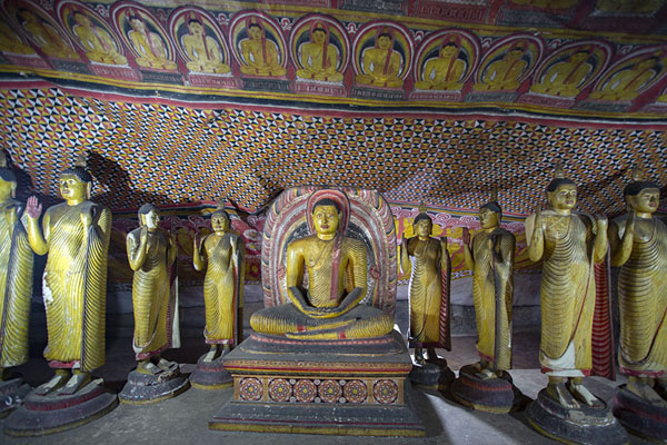 Seated Buddha surrounded by standing Buddhas in the largest cave: Maha Raja Viharaya | Dambulla Cave Temple | Sri Lanka