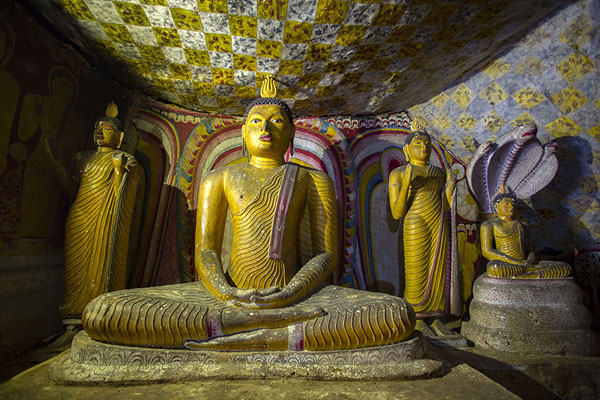 Statues of Buddha, one under a cobra, in the third, or Maha Alut Viharaya, cave | Templo de la Cueva de Dambula | Sri Lanka