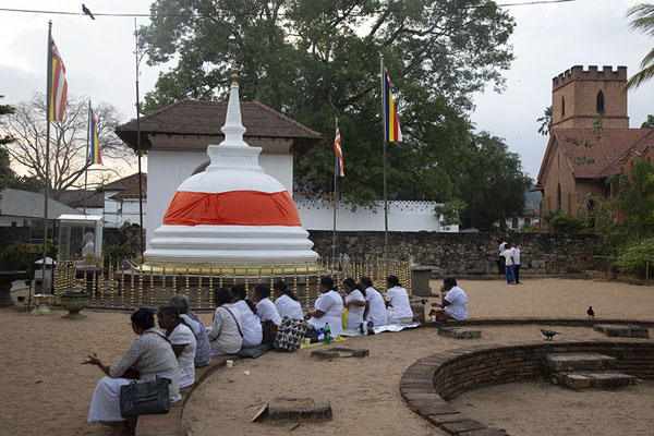 People sitting in a semi-circle in the temple grounds directly west of the Temple of the Sacred Tooth | Templo del Dente de Buda | Sri Lanka