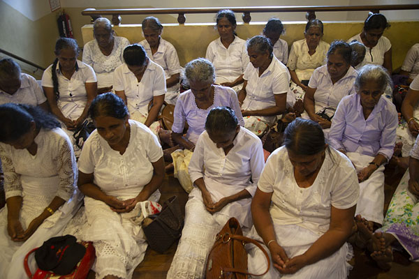 Women sitting on the floor in prayer in the Temple of the Sacred Tooth Relic | Templo del Dente de Buda | Sri Lanka