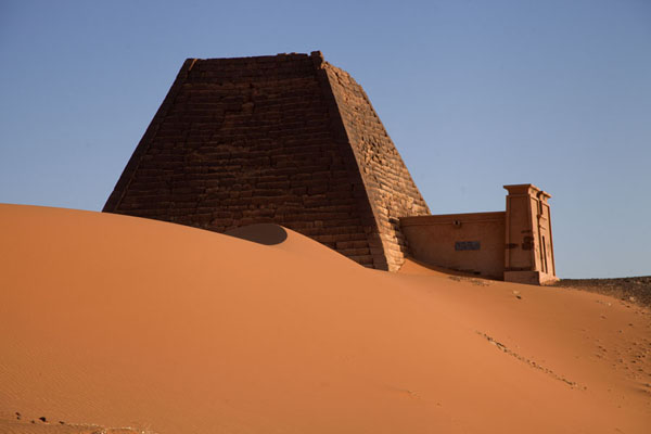 Foto van One of the pyramids and a sand dune at sunriseBegrawiya - Soedan