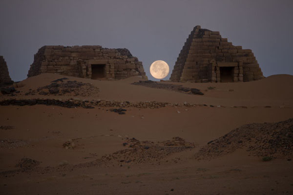 Foto van Full moon sinking between two pyramidsBegrawiya - Soedan