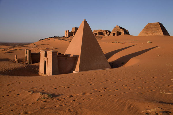 Foto van Early morning light casting shadows of the pyramids on the sand - Soedan - Afrika