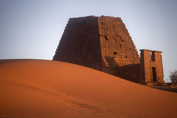 Sunrise over a sand dune and one of the pyramids of the northern cemetery | Pirámides de Begrawiya | Sudán