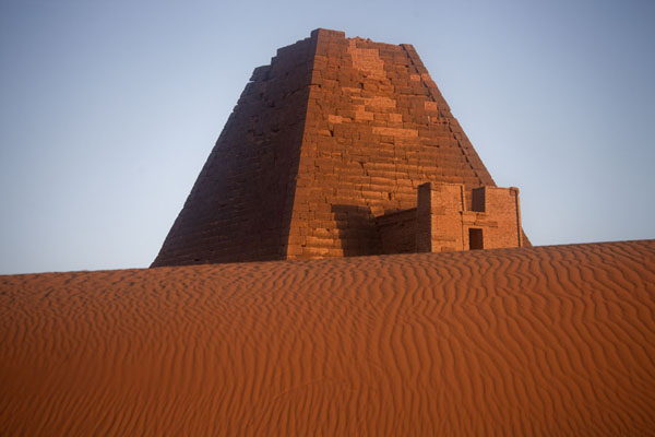 的照片 Sand dune with a pyramid in the background at sunrise - 苏丹