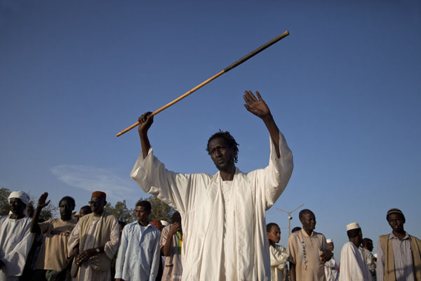 One of the dervishes raising his arms with a wooden cane | Hamed El Nil dervishes | Sudan