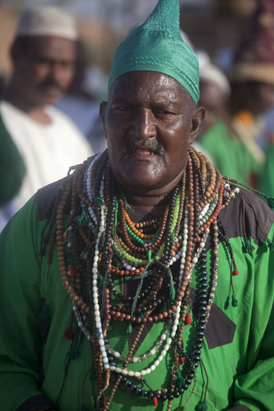 One of the dervishes dressed in green and with lots of prayer beads around his neck | Hamed El Nil dervishes | Sudan