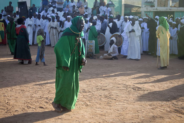 Dervish dressed in green with the musicians in the background | Hamed El Nil dervishes | Sudan