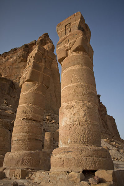 Picture of Columns with carved faces at the entrance of the Temple of Mut and at the foot of Jebel Barkal