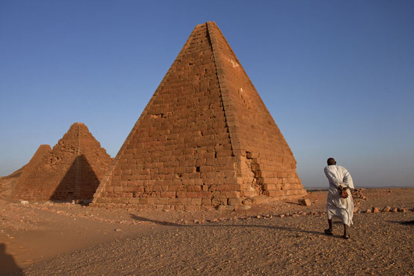 Picture of Caretaker walking towards the pyramids near Jebel Barkal in the late afternoon - Sudan - Africa