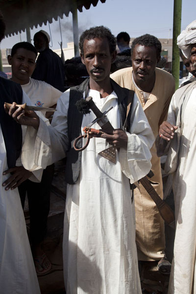 Beja men showing one of their famous swords and a dagger to the visitor | Marchés de Kassala | Soudan