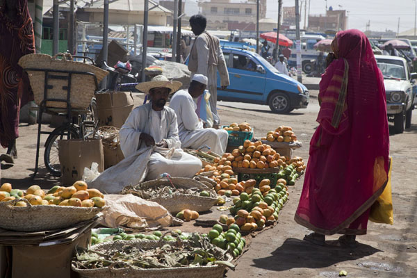 Veiled woman walking past fruit being sold at one of the markets of Kassala | Marchés de Kassala | Soudan