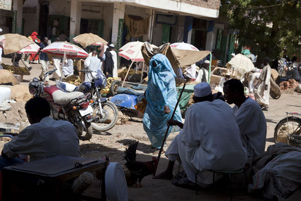 Picture of Street scene of one of the markets of Kassala with men drinking tea and veiled woman walking by